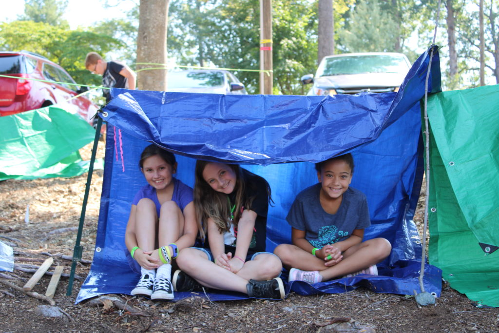 From left to right, Sierra Wood, Summer Chester and Zoe Woods sit together under their tarp shelter at a Caldwell County 4-H 2019 Summer Exploring class, where youth learned outdoor survival skills from the County Emergency Response Team. Youth their age enjoy belonging and working in groups.