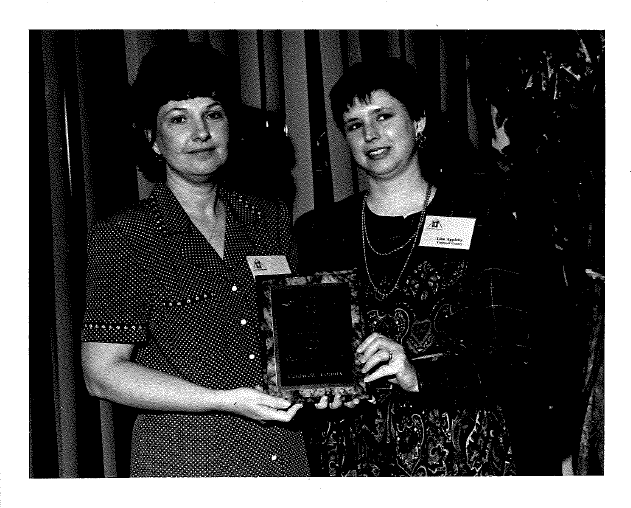 Debbie Johnston and Lisa Appleby receive a 1997 Volunteer Leadership Team Award on behalf of the Oak Hill 4-H Club.