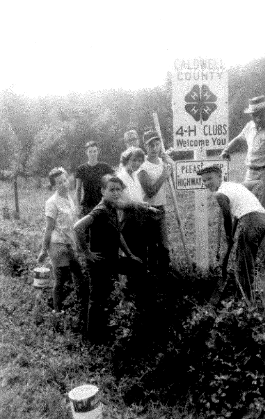 From the archives, a photo shows former 4-H members installing a welcome sign in Caldwell County