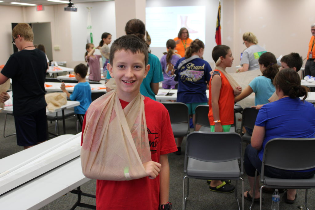 Locke Sholar shows off sling-making skills during a summer 4-H class with the Caldwell County Community Emergency Response Team. Today 4-H teaches youth about agriculture and other subjects, such as healthy living and safety.