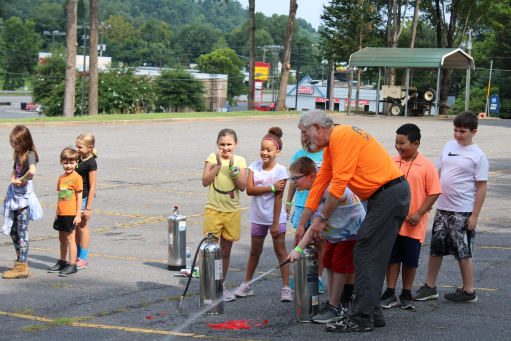 Irv Kanode, volunteer with Caldwell County's Community Emergency Response Team, shows a 4-H member during a summer program how to correctly use a fire extinguisher.
