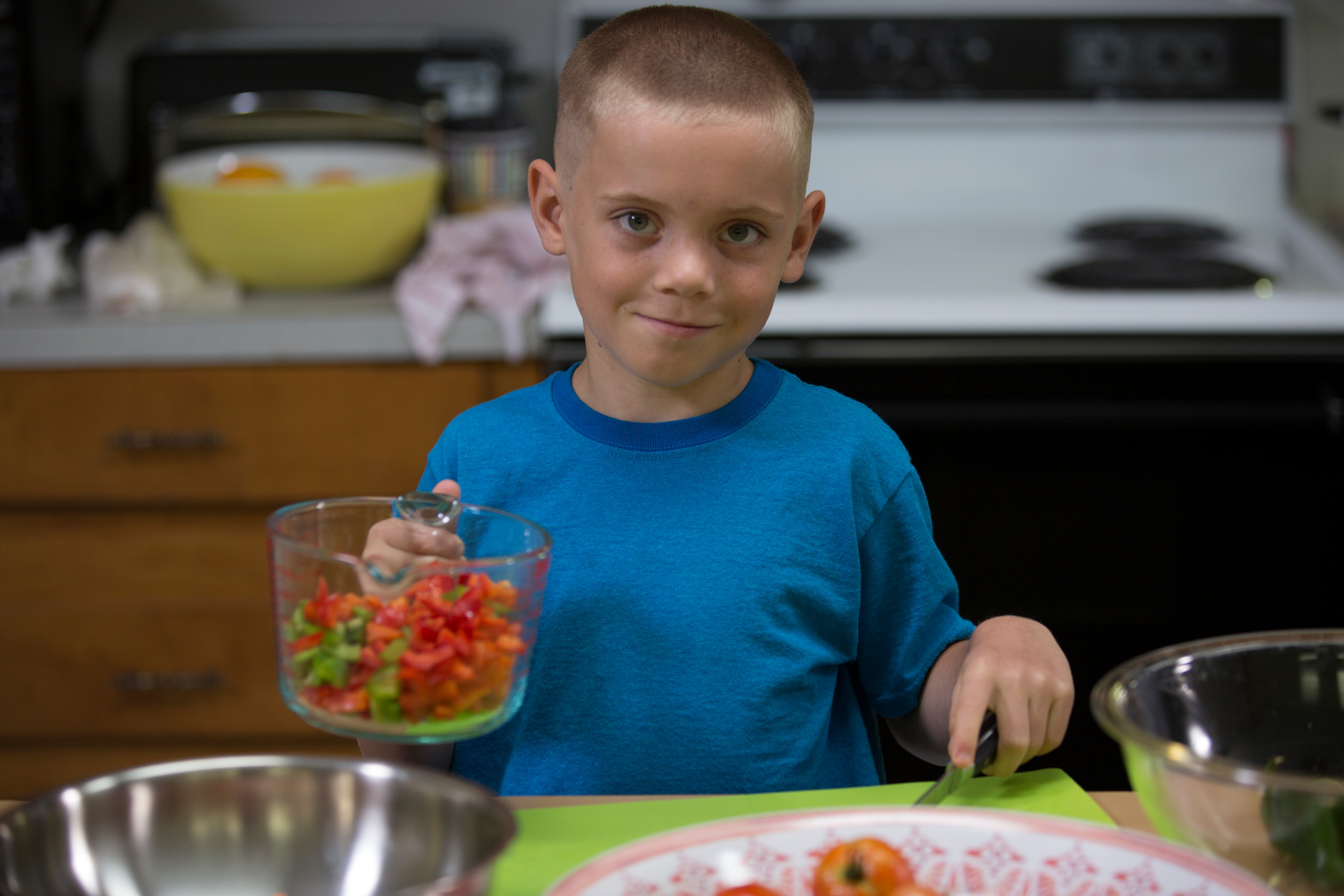 A boy prepares fruits and vegetables in the kitchen. A mystery fruit and veggie taste test is one activity families can try this summer as a way to spend quality time together.