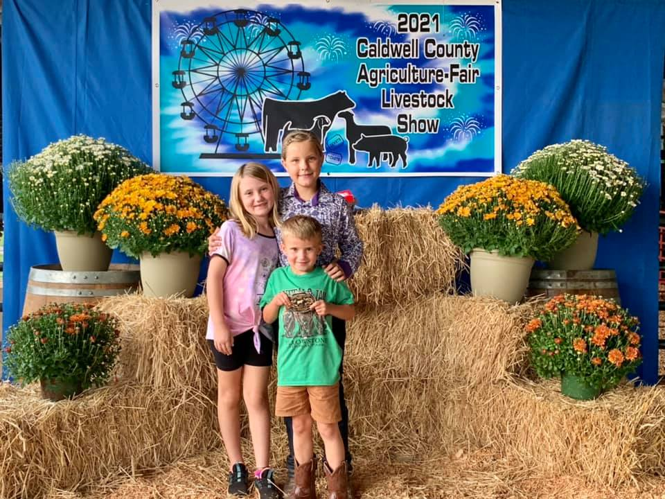 Shelby and Harrison Ford pose with Peyton Taylor and the Caldwell Agriculture Fair. All three work with and show livestock.