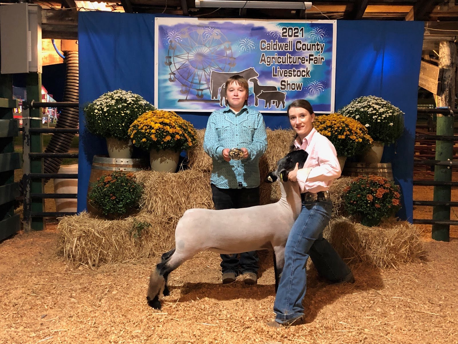 Eli and Addie Dillon pose in the barn after Addie won the senior showmanship division at the the fair's sheep show.
