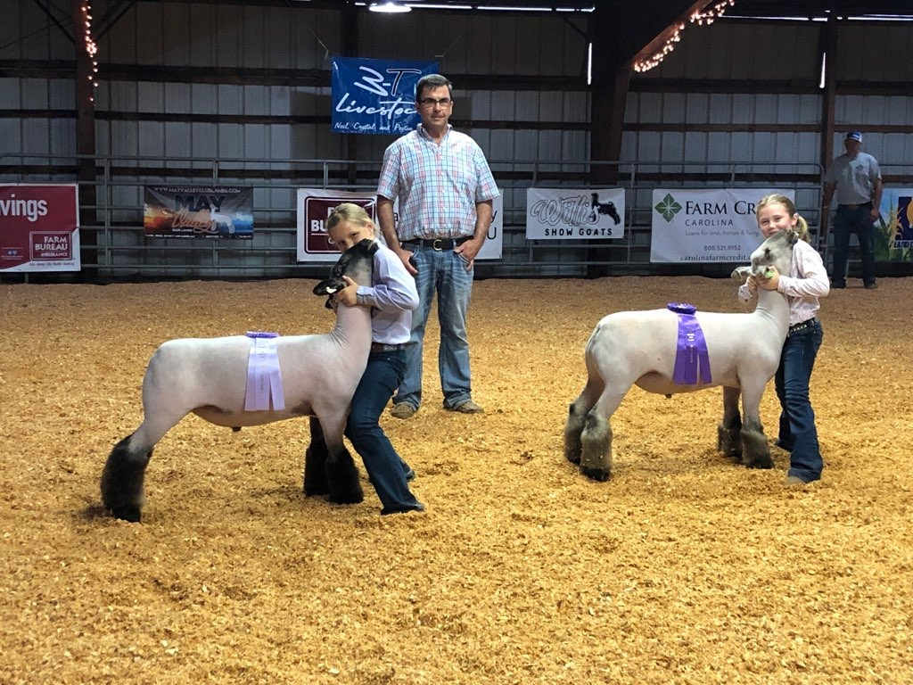 Two Caldwell County youth pose with the judge after winning champion and reserve market lambs at the 2021 fair. Peyton Taylor, left, showed the one in reserve; and Shelby Ford, right, showed the champion.